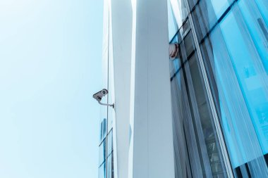 View of a contemporary surveillance video cam attached to a metal girder of the facade of a modern business skyscraper; security video camera on the frontage of an office high-rise with the sky behind