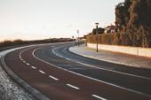 Fotografie Die Aussicht auf eine leere ordentlich zweispurigen Straße macht eine Drehung nach rechts, Straßenmarkierung, Fahrradweg, Laternen und Gehwege Pflaster Stein, geringe Schärfentiefe Abend in Cascais, Portugal