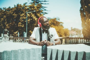 Handsome mature bearded bald African man in glasses and an elegant white suit is enjoying sunny summer weather, standing outdoors, and listening to music in his reddish headphones