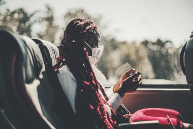 A black woman in a virus protective face mask and with long braided hair of red color is sitting on a leather seat of a regular intercity bus and watching an online show using her smartphone