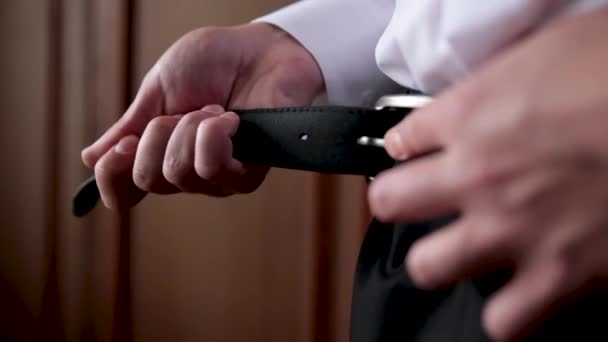 The young man corrects a belt on trousers.