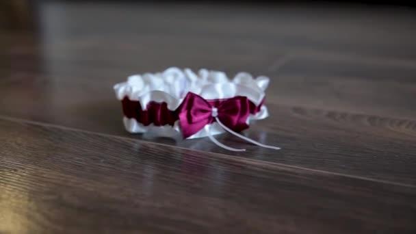 Weiße Hochzeitsgarter mit einem lila Bogen für die schöne Braut.