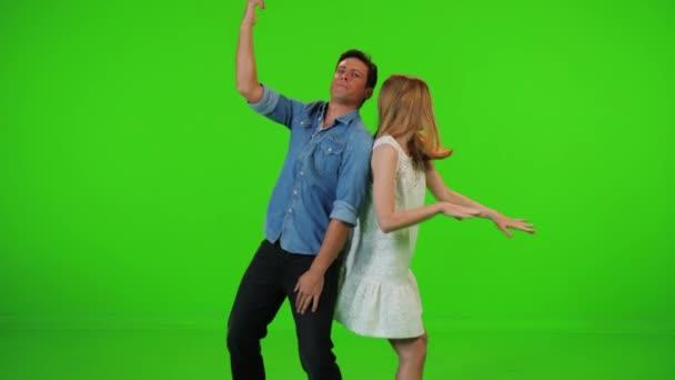 Zeitlupe Paar tanzt fröhlich zusammen auf einer Party zu einem Hip-Hop-Beat über eine grüne Leinwand.