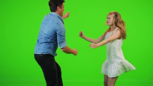 Paar tanzt fröhlich in Zeitlupe über grüne Leinwand.