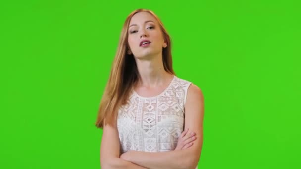 beautiful woman looks dramatically into the lens, then laughs and acts playful, over a green screen, medium shot.
