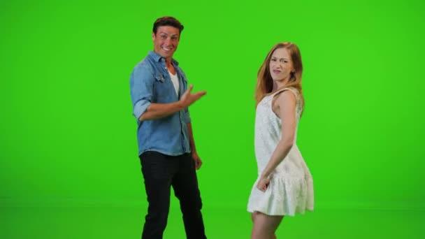 In Zeitlupe tanzt das Paar fröhlich zusammen auf einer Party zu einem Hip-Hop-Beat, blickt lächelnd in die Kamera. über einen grünen Bildschirm.