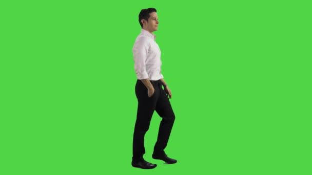 Young businessman using an app, getting some amazing news, excited, walking sideways over a greenscreen. Two takes.