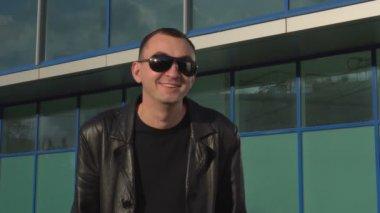 248d85de0a Νεαρός άνδρας σε δερμάτινο μπουφάν και γυαλιά ηλίου έκπληκτος εξωτερική  Βίντεο Κλιπ
