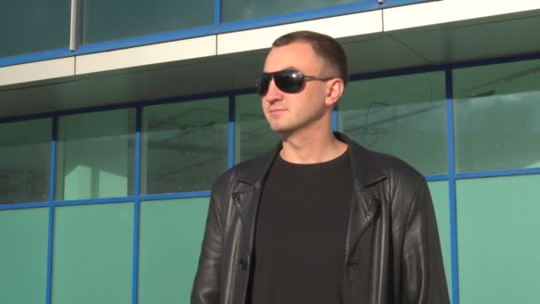 Side view of young man in leather jacket and sunglasses standing outdoor
