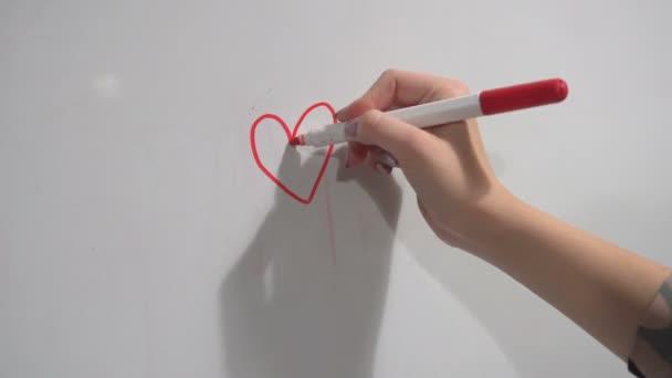 Női kéz filccel gyorsan felhívja a szív műanyag tábla.