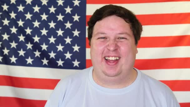 Young man holds back laughter on the background of an USA flag