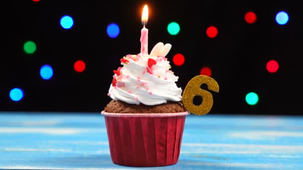 köstliche Geburtstagstorte mit brennender Kerze und Zahl 6 auf buntem verschwommenem Lichterhintergrund