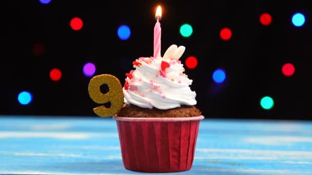 köstliche Geburtstagstorte mit brennender Kerze und Zahl 9 auf buntem verschwommenem Lichterhintergrund