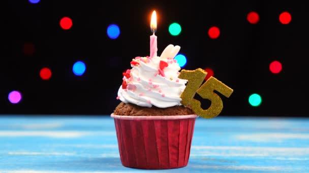 Výborný narozeninový dort s hořící svíčkou a číslo 15 na pozadí barevných rozmazaných světel