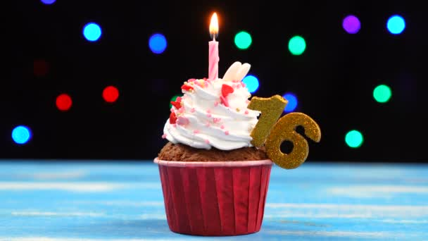 Výborný narozeninový dort s hořící svíčkou a číslo 16 na pozadí barevných rozmazaných světel