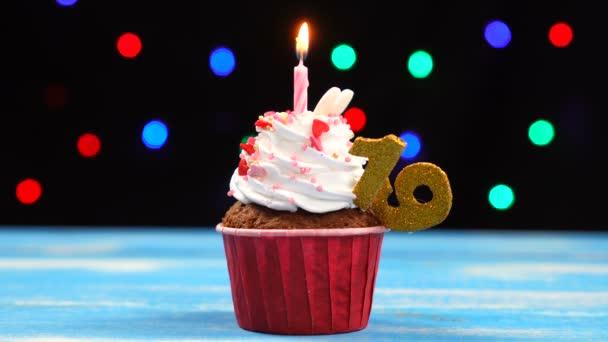 Ízletes születésnapi Cupcake égő gyertyát, és a szám 19 a sokszínű homályos fények háttér