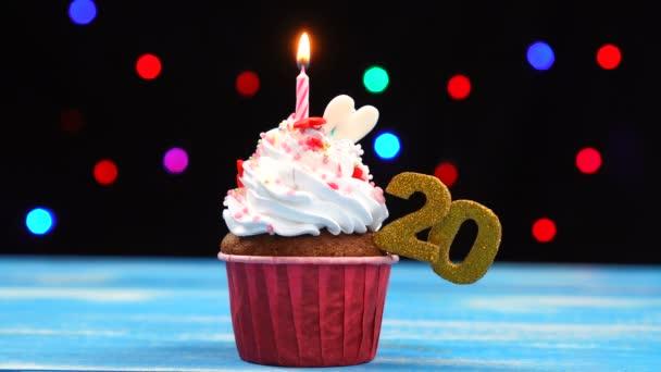 Ízletes születésnapi Cupcake égő gyertyát, és a szám 20 a sokszínű homályos fények háttér