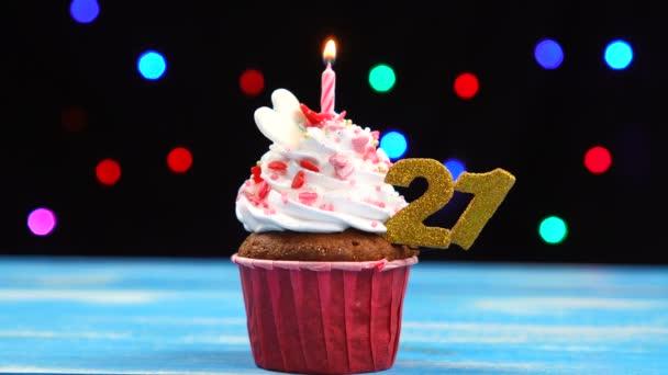 köstliche Geburtstagstorte mit brennender Kerze und Zahl 21 auf buntem verschwommenem Lichterhintergrund