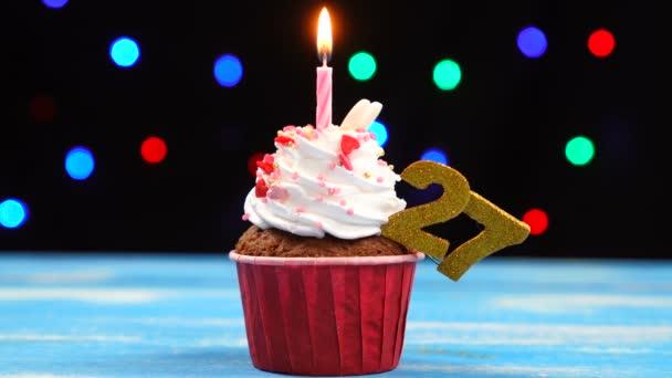 Výborný narozeninový dort s hořící svíčkou a číslo 27 na pozadí barevných rozmazaných světel