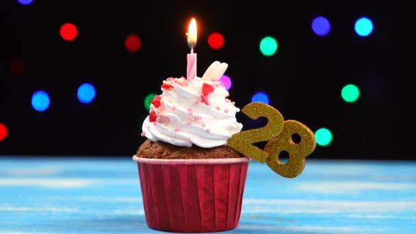 köstliche Geburtstagstorte mit brennender Kerze und Zahl 28 auf buntem verschwommenem Lichterhintergrund