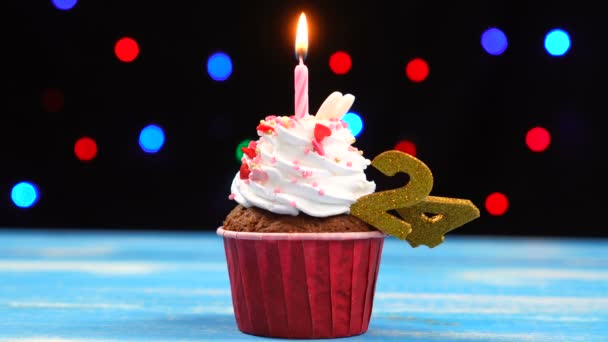 Delicious birthday cupcake with burning candle and number 24 on multicolored blurred lights background