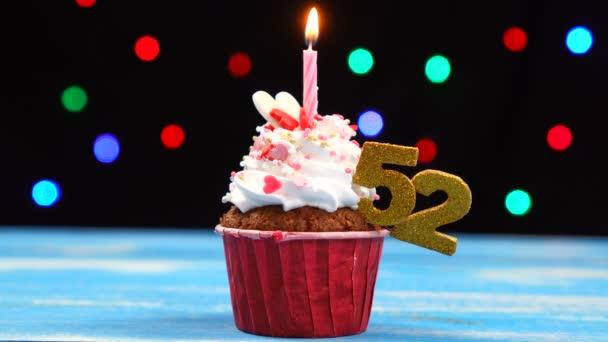 Výborný narozeninový dort s hořící svíčkou a číslo 52 na pozadí barevných rozmazaných světel