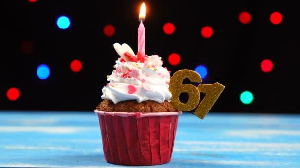 Delicious születésnapi Cupcake égő gyertyát, és a szám 61 a többszínű homályos fények háttér