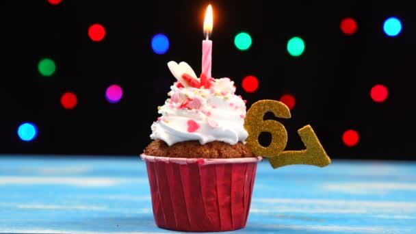 Výborný narozeninový dort s hořící svíčkou a číslo 67 na pozadí barevných rozmazaných světel