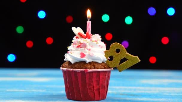 Delicious születésnapi Cupcake égő gyertyát, és a szám 81 a többszínű homályos fények háttér