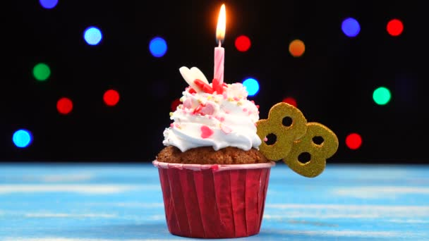 Výborný narozeninový dort s hořící svíčkou a číslo 88 na pozadí barevných rozmazaných světel