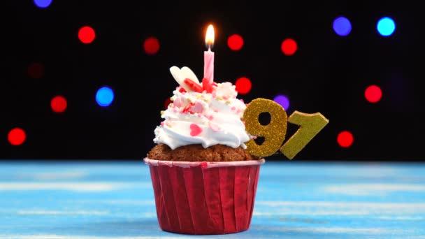 köstliche Geburtstagstorte mit brennender Kerze und Zahl 91 auf buntem verschwommenem Lichterhintergrund