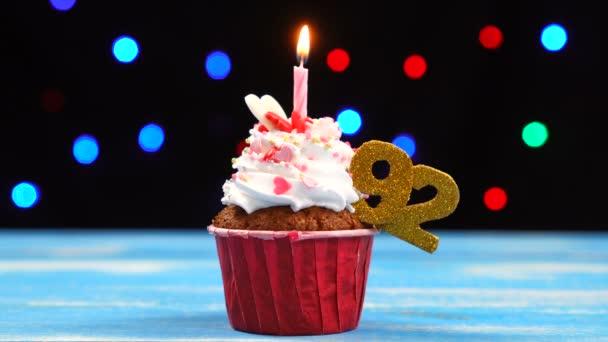 Výborný narozeninový dort s hořící svíčkou a číslo 92 na pozadí barevných rozmazaných světel