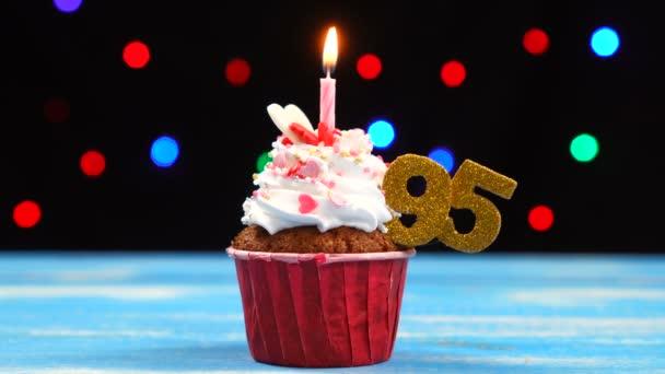 köstliche Geburtstagstorte mit brennender Kerze und Zahl 95 auf buntem verschwommenem Lichterhintergrund