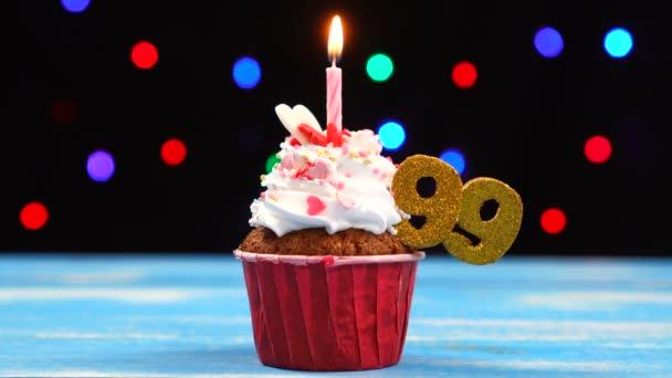 Výborný narozeninový dort s hořící svíčkou a číslo 99 na pozadí barevných rozmazaných světel
