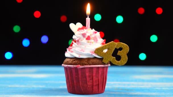 Delicious születésnapi Cupcake égő gyertyát, és a szám 43 a többszínű homályos fények háttér