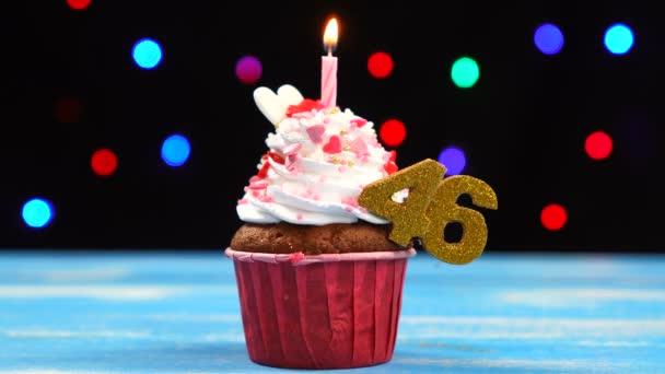 köstliche Geburtstagstorte mit brennender Kerze und Zahl 46 auf buntem verschwommenem Lichterhintergrund