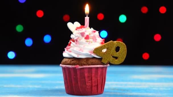 Výborný narozeninový dort s hořící svíčkou a číslo 49 na pozadí barevných rozmazaných světel