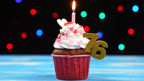 köstliche Geburtstagstorte mit brennender Kerze und Zahl 76 auf buntem verschwommenem Lichterhintergrund