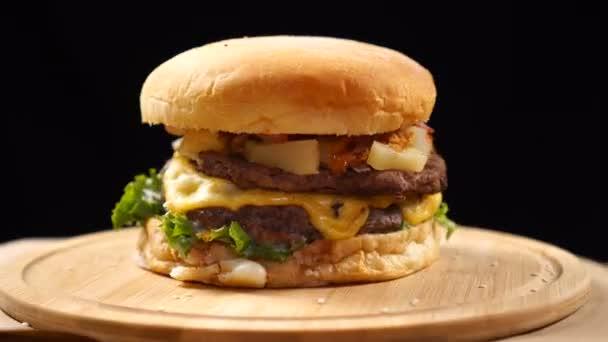 Velký šťavnatý hamburger se sýrem, omáčkou a zeleninou, otáčející se na dřevěné desce na černém pozadí