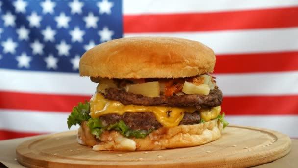 Čerstvý šťavnatý Burger se sýrem, omáčkou a zeleninou otáčející se na dřevěné desce na americké vlajce.