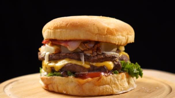 Čerstvý šťavnatý hamburger, který se otáčí na černém pozadí.