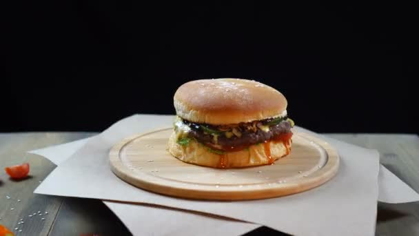 Čerstvý šťavnatý hamburger se rychle otáčí na černém pozadí.