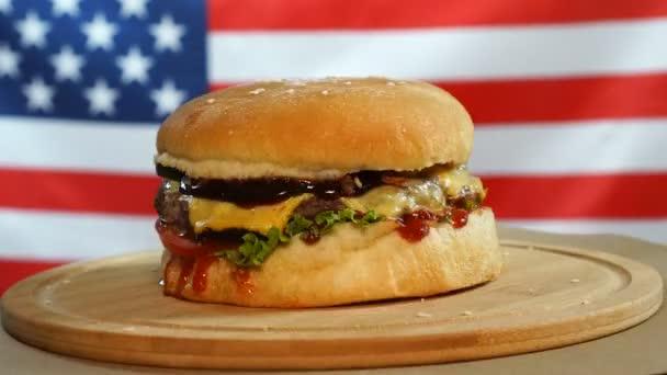 Čerstvý šťavnatý Burger se rychle otáčí na pozadí vlajky USA.