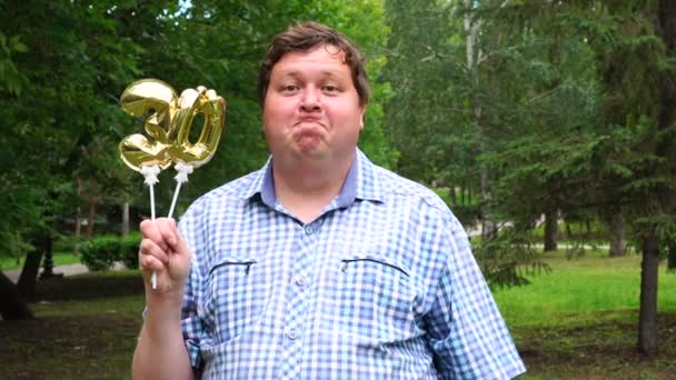 Big man holding golden balloons making the 30 number outdoor. 30th anniversary celebration party