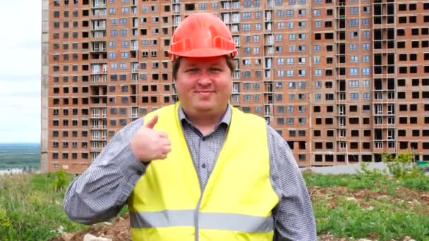Male builder foreman, worker or architect on construction building site showing thumb up and looking to camera