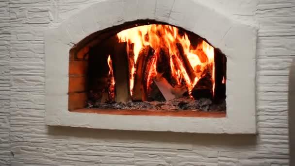 Dřevo hoří v útulném krbu doma ve vnitrozemí. Krb jako kus nábytku
