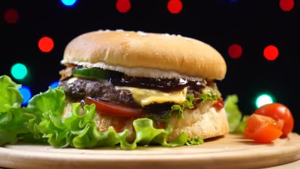 Chladný nádherný čerstvý šťavnatý Burger se otáčí na otočný stůl na pozadí barevných rozmazlných světel.