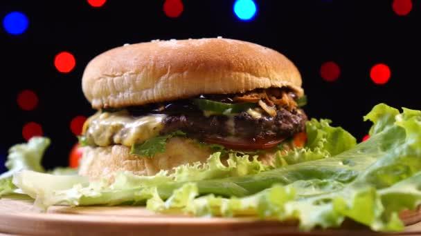 cool schöne frische saftige gekochte Burger drehen sich auf Plattenteller vor einem Hintergrund von bunten verschwommenen Lichtern.