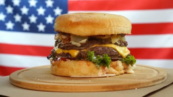 Burger s hovězím, sýrem a zeleninou se otáčí na dřevěné desce proti pozadí vlajky USA