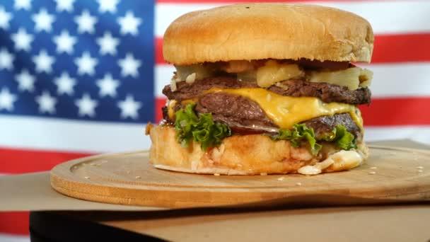 Grilovaný americký hovězí Burger s hlávkovým salátem, sýrem, cibulkou podávané na dřevěném papíře, který se otáčí na dřevěné přepážce.